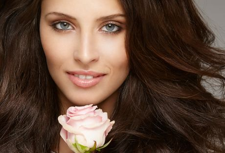 Beautiful brunette woman holding rose
