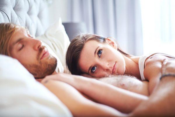 Pensive woman laying on sleeping man on bed