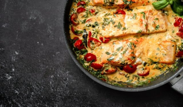 Close up of delicious tuscan cream salmon with spinach and cherry tomato in a pan on black background