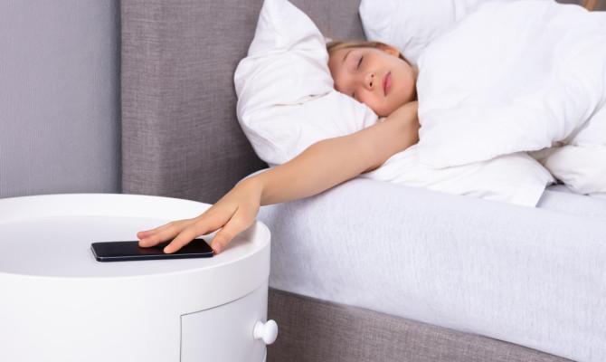 Girl Snoozing Alarm On Cellphone