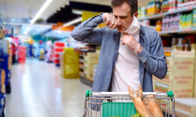 Neglected man touching his face under the mask buying in a supermarket with a cart full of food