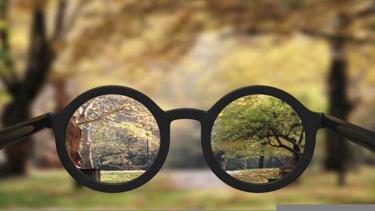 Closeup,On,Eyeglasses,With,Focused,And,Blurred,Landscape,View.