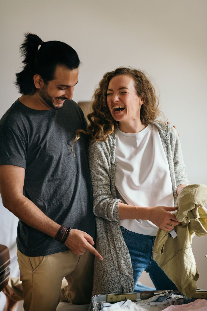 diverse-couple-laughing-while-packing-suitcases-for-holiday-4247722-830x0