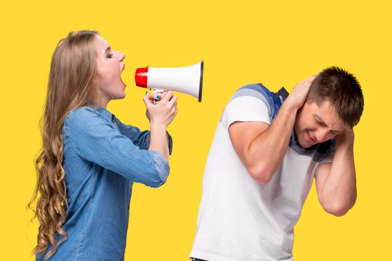 Woman shouting in megaphones at each other