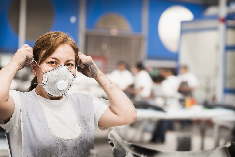 Worker wearing face mask in manufacturing plant