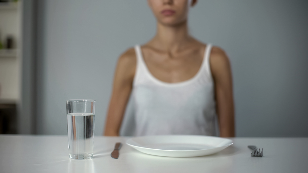 Anorexic girl sitting in front of empty plate, drinking water, severe diet