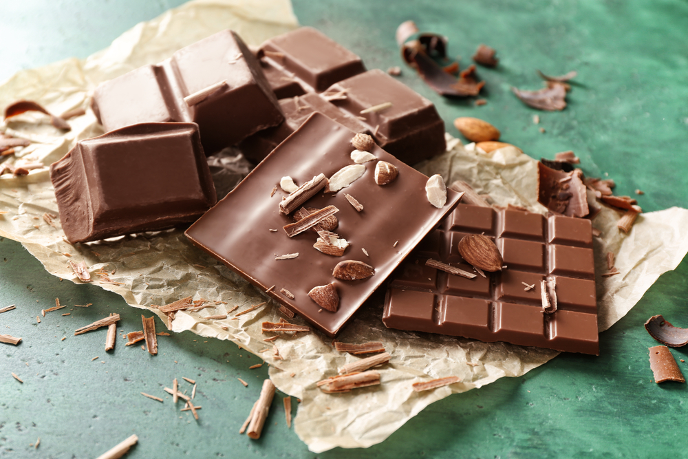 Tasty milk chocolate with almonds on parchment