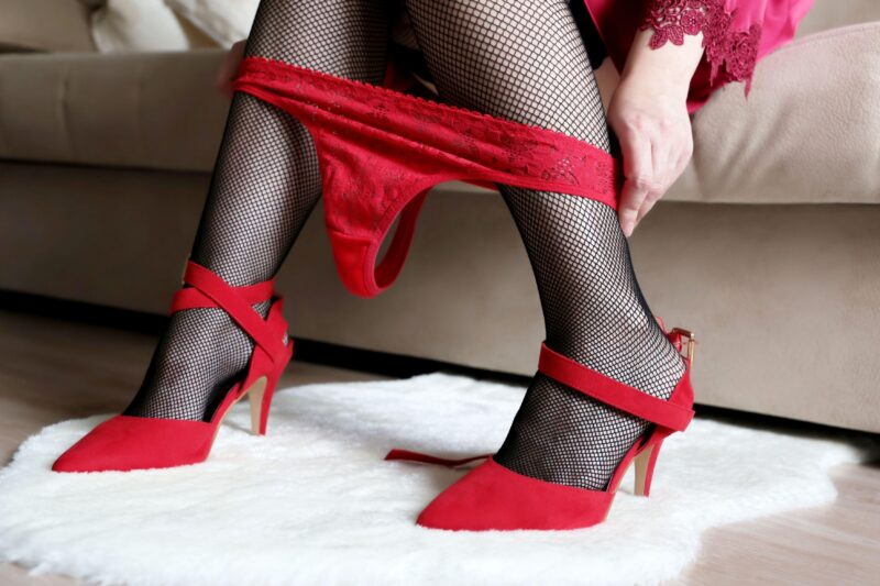 Female legs near the bed, seductive lingerie. Woman in black fishnet stockings takes off her red panties