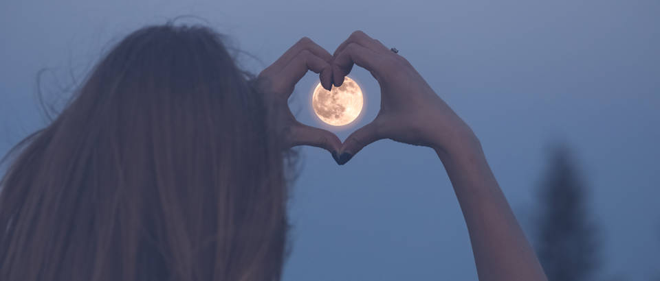 Woman,Making,Heart,Shape,With,Her,Hands,Over,Full,Moon.