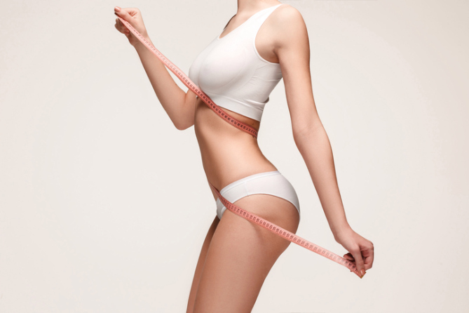 The girl taking measurements of her body, white background