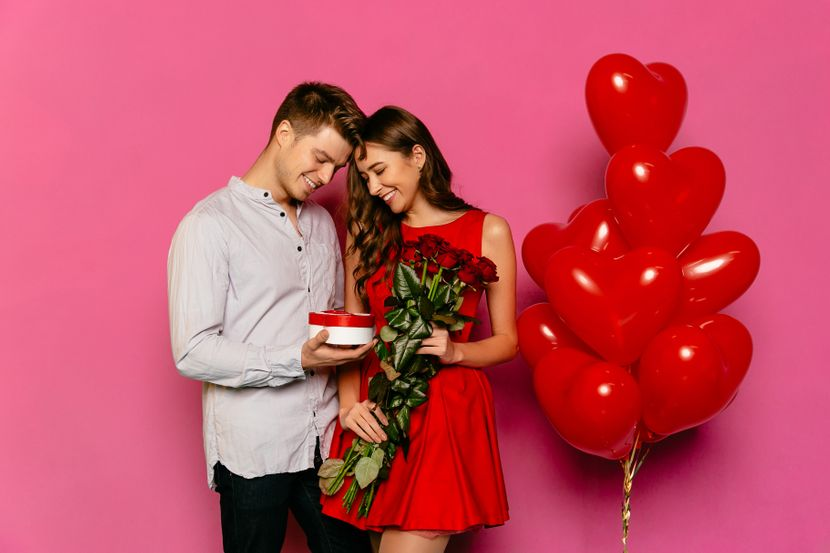 handsome-man-attractive-woman-looking-box-with-gift-red-roses-830x0