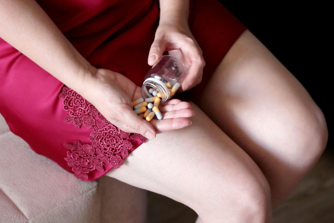 Woman taking pills, bottle of capsules in female hands. Woman in red nightie sitting on the sofa, concept of sleeping or slimming pills