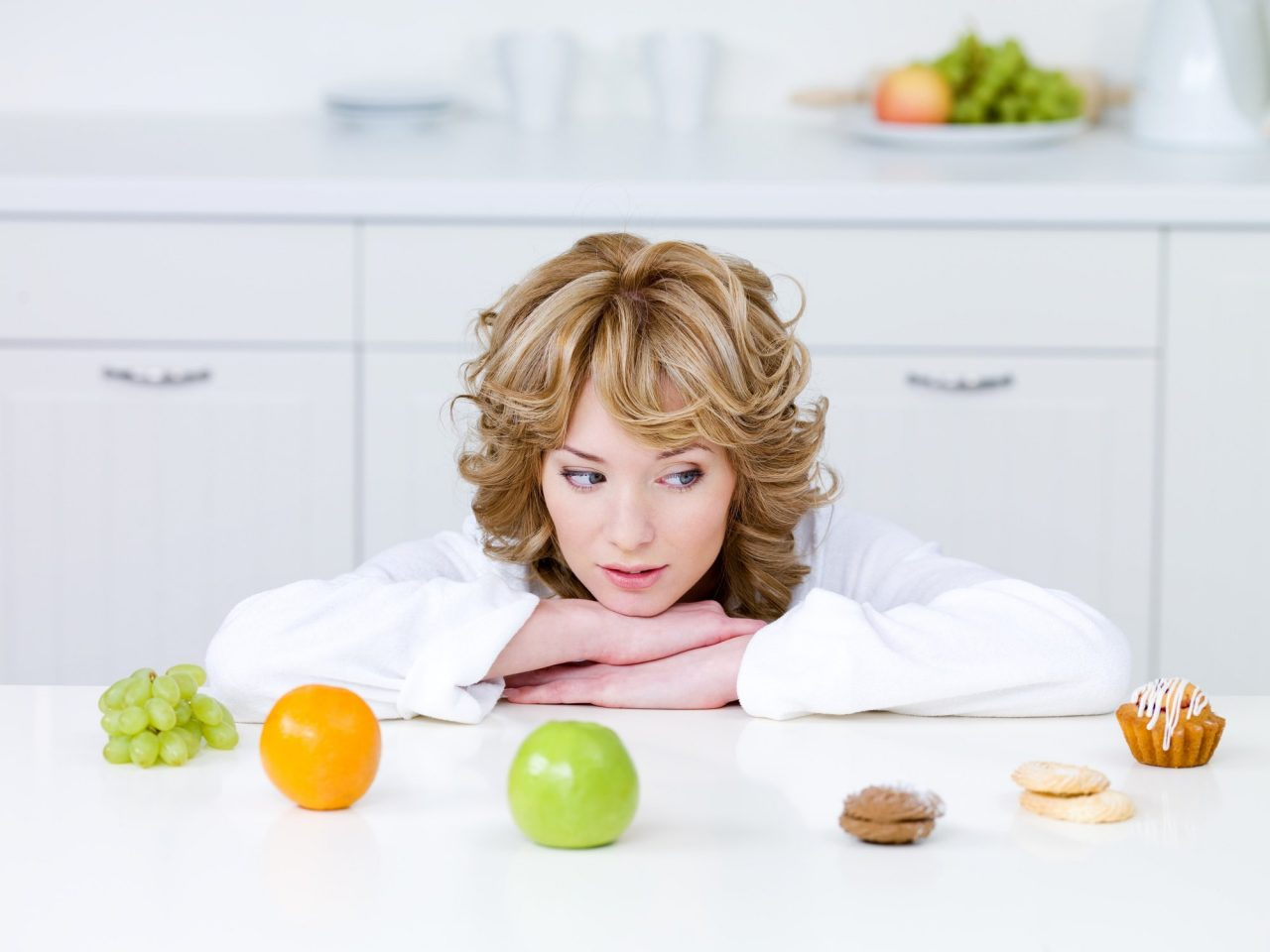 beautiful-young-woman-sitting-kitchen-choosing-healthy-fruits-tasty-cakes