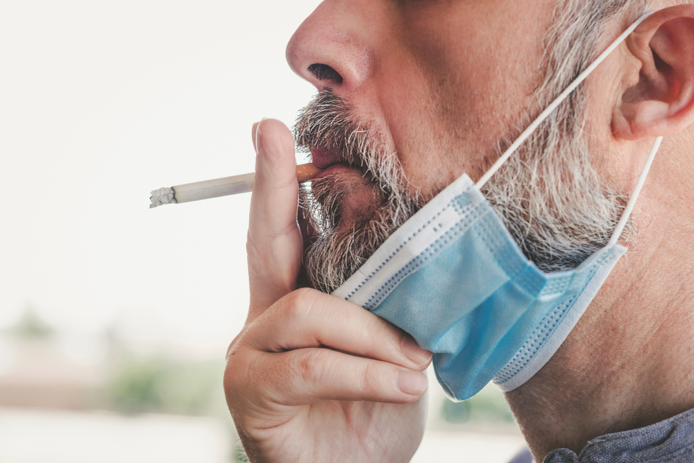 Covid-19,close-up,Of,Man,With,Medical,Mask,Smoking,A,Cigarette,At