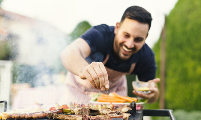 Smiling,Man,Seasoning,Meat,On,The,Grill