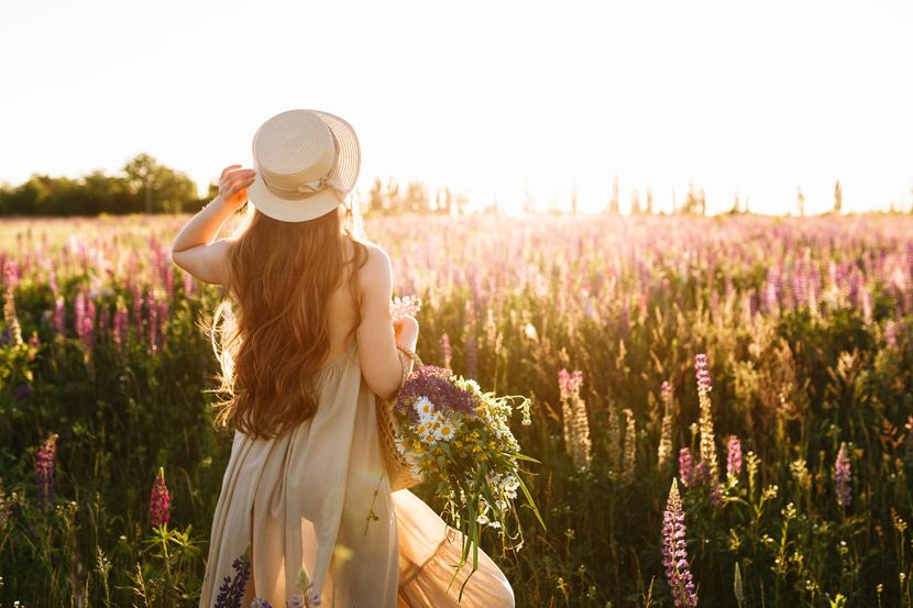 young-woman-straw-hat-dress-with-bouquet-lupine-flowers-830x0