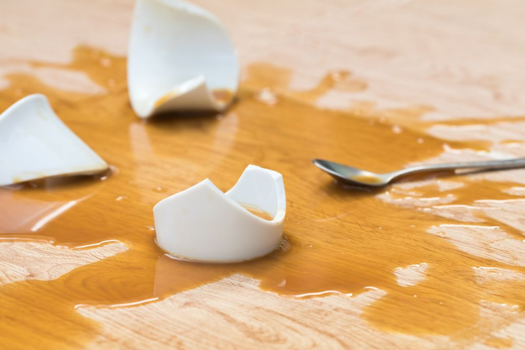 Coffee,In,White,Cup,Spilled,With,Broken,On,Wooden,Background