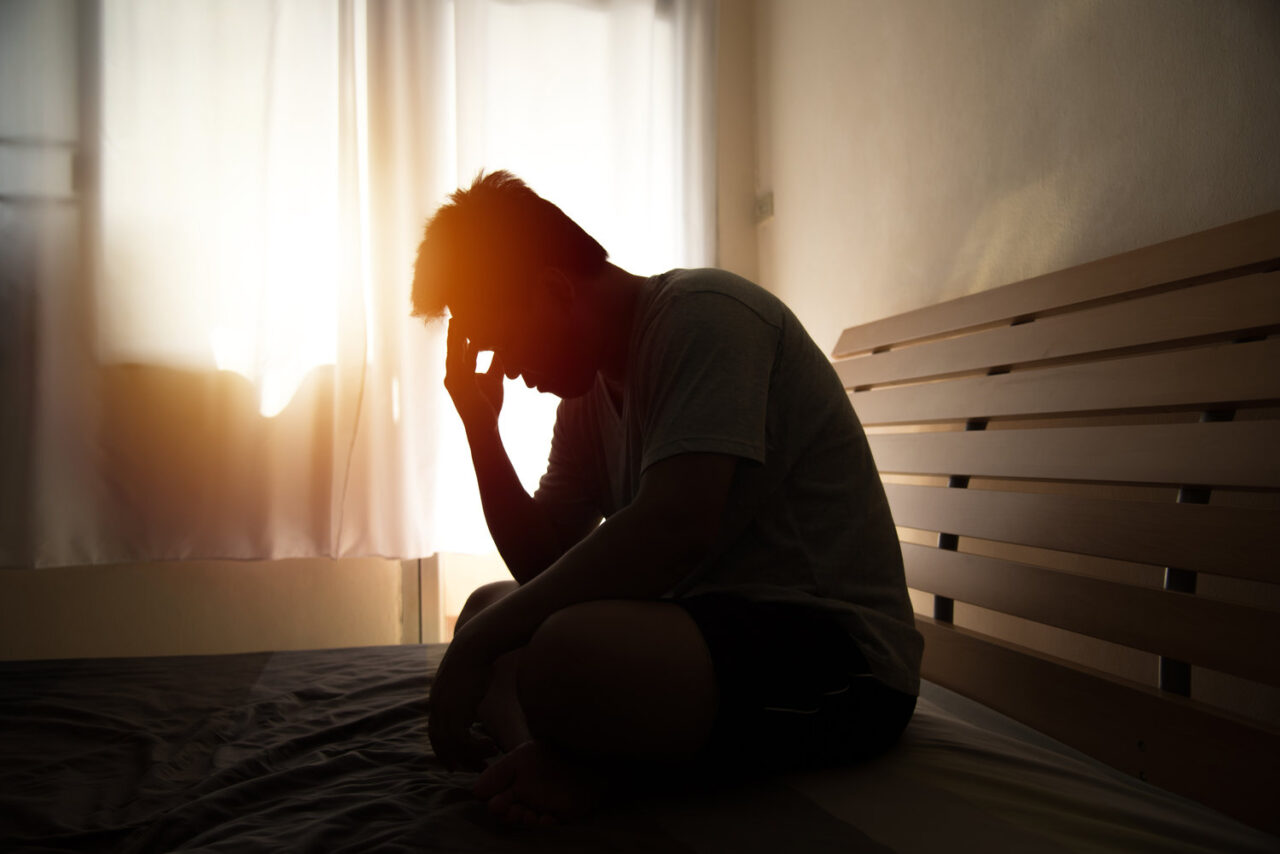 desperate man in silhouette sitting on the bed with hands on head , headache after weak up