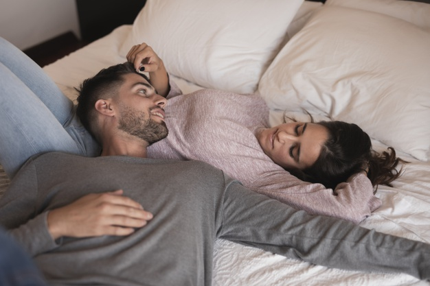 beautiful-couple-laying-bed_23-2148329382