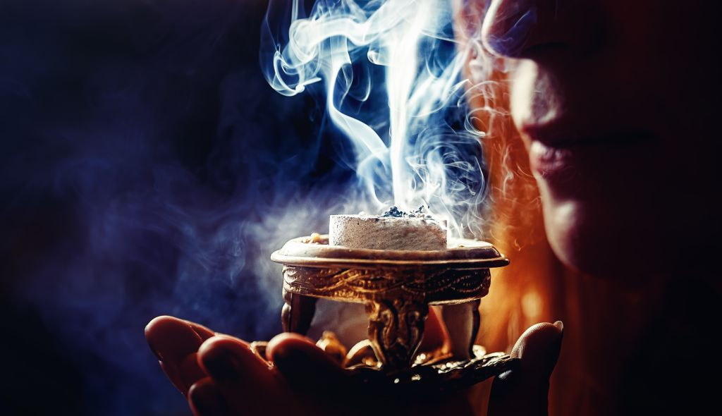 Incense,In,A,Woman,Hand,,Incense,Smoke,On,A,Black