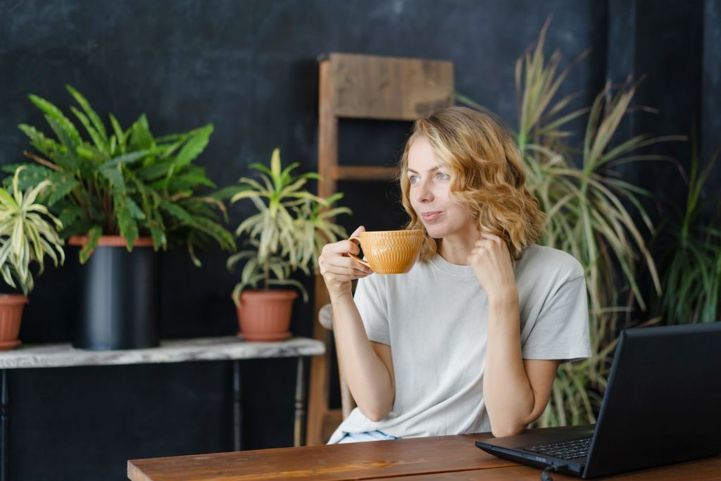 A,Woman,Drinks,Coffee,And,Enjoys,At,Her,Work,Desk